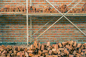 New interior red brick wall with scaffolding under construction texture background.