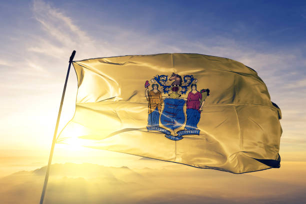 New Jersey state of United States flag textile cloth fabric waving on the top sunrise mist fog stock photo