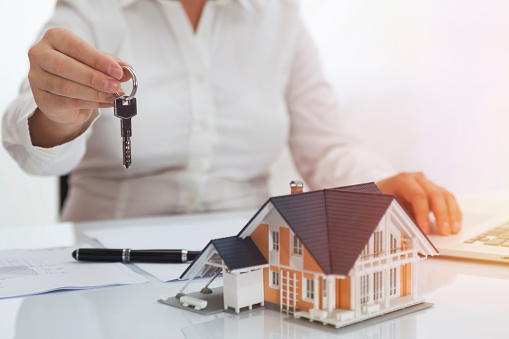 Real estate agent holding key with house model