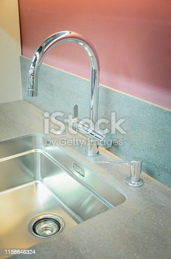 A new kitchen sink with an artificial stone countertop. The concept of modern kitchen interior. Vertical photography.