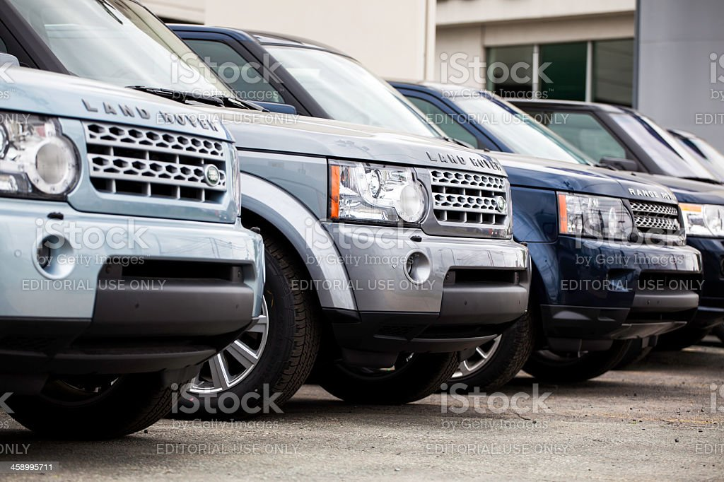 New Land Rover Vehicles in a Row Halifax, Nova Scotia, Canada - June 3, 2012: New Land Rover vehicles at a car dealership.  Various colors of Land Rover models continue in the row of vehicles.  Dealership building visible in background.  Land Rover manufacturers a range of four-wheel drive vehicles including the pictured Land Rover and Range Rover, as well as the Defender, and Evoque to name a few. 4x4 Stock Photo