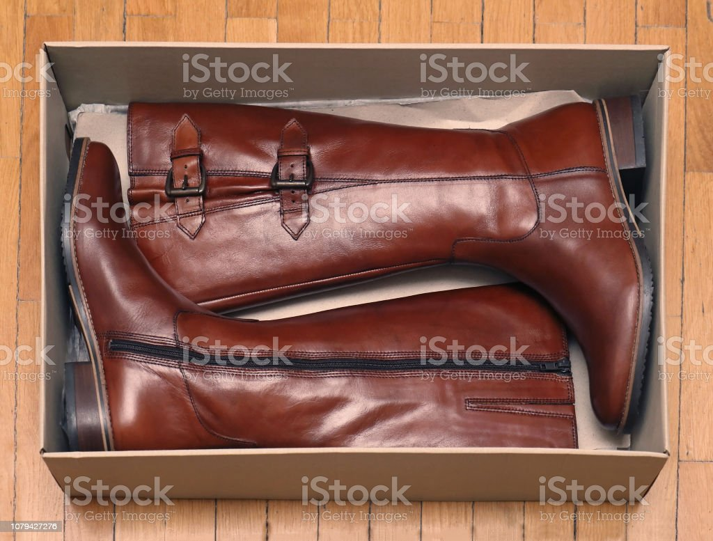 New brown leather modern female boots inside box on wooden floor