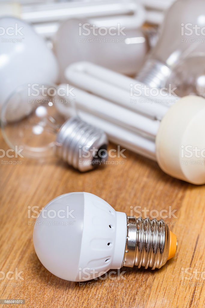new LED lamp and pile of old bulbs on board stock photo