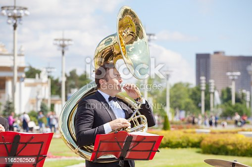 Moscow, Russia - June 16, 2019: New Life Brass band, wind musical instrument player, orchestra performs music, man musician plays sousaphone, trumpeter in black suit blowing helicon tube, VDNKh park