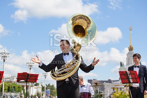 Moscow, Russia - June 16, 2019: New Life Brass band, wind musical instrument player, orchestra performs music, man musician plays sousaphone, trumpeter in black suit with helicon tube, VDNKh park