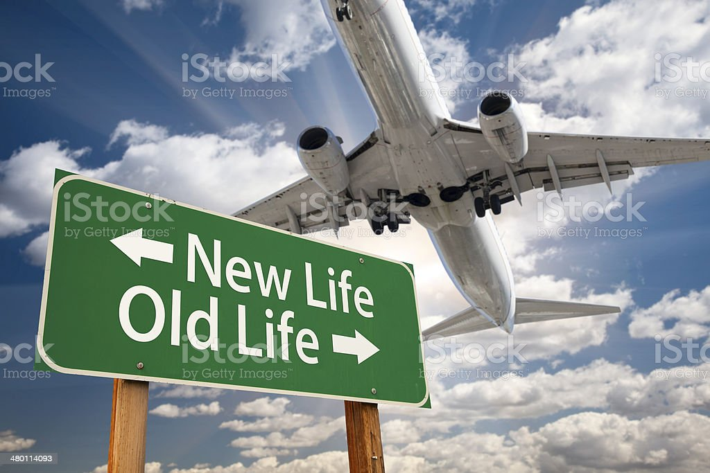 New Life, Old Life Green Road Sign and Airplane Above with Dramatic...