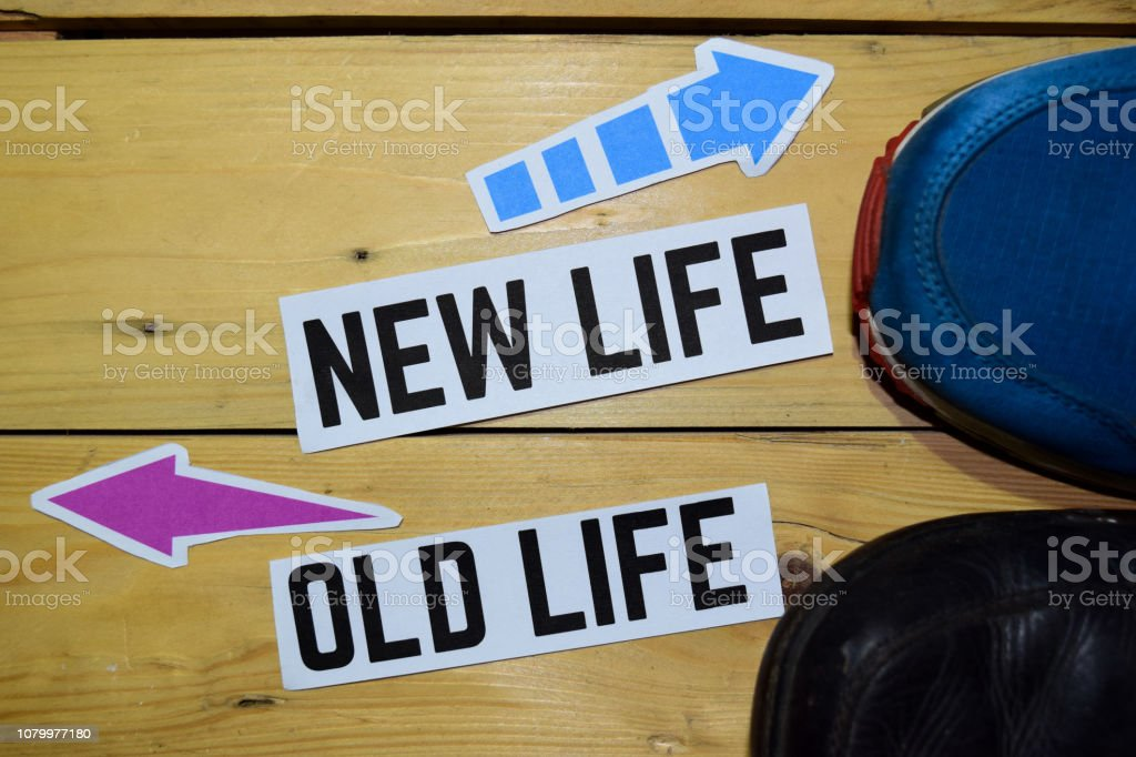 New Life or Old Life opposite direction signs with sneakers on wooden...