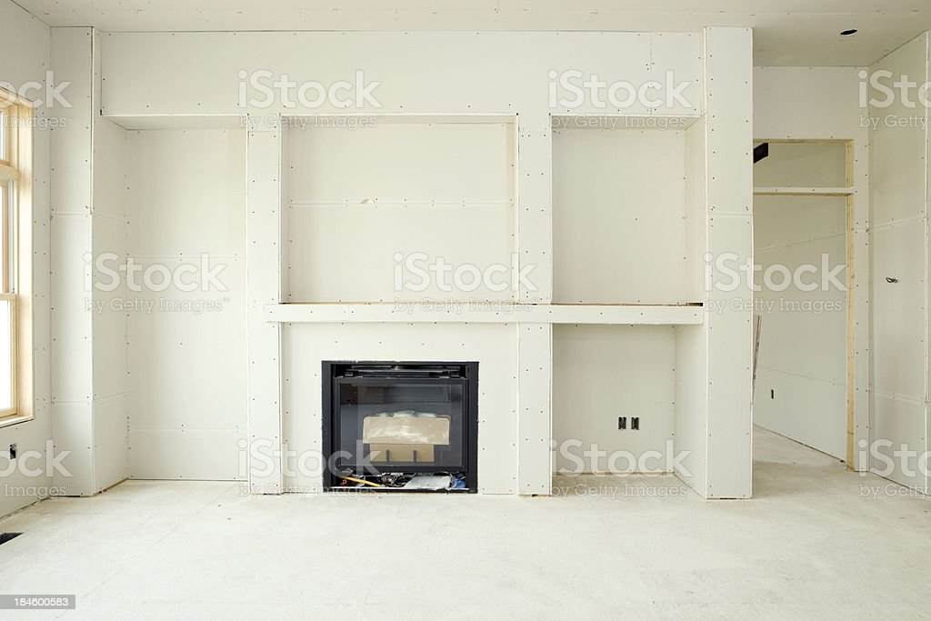 New Living Room Drywall with Fireplace and Built-in Shelves stock photo