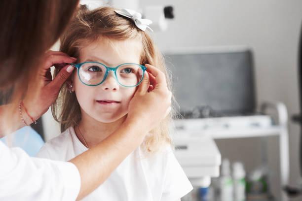 yeni bir görünüm. doktor vizyonu için çocuk yeni gözlük veren - gözlük stok fotoğraflar ve resimler