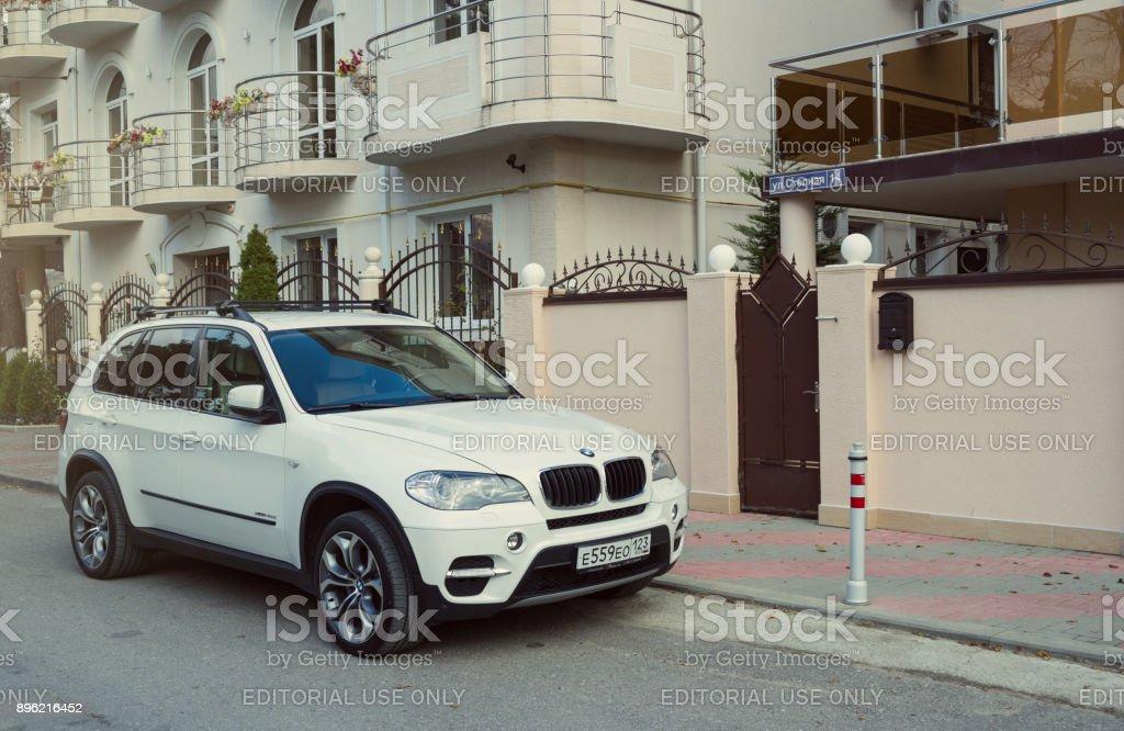 New luxury BMW x5 parked near house. stock photo