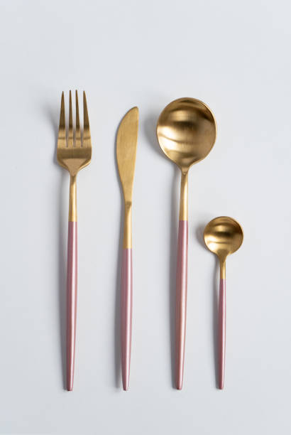 new luxury golden cutlery view from above on a isolated white background. top view. pink knife, fork and spoon for a festive table for a wedding, birthday or party. - łyżka sztućce zdjęcia i obrazy z banku zdjęć