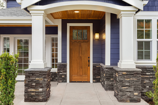 New Luxury Home Exterior Detail Patio And Front Door With Arch And Columns Stonework Graces The Bottom Of The Columns And House While White Columns And Archway Provide A Stately Welcome Stock Photo - Download Image Now