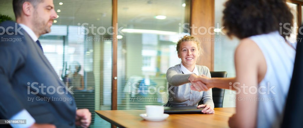 a young woman sits opposite the recruitment manager and shakes her...