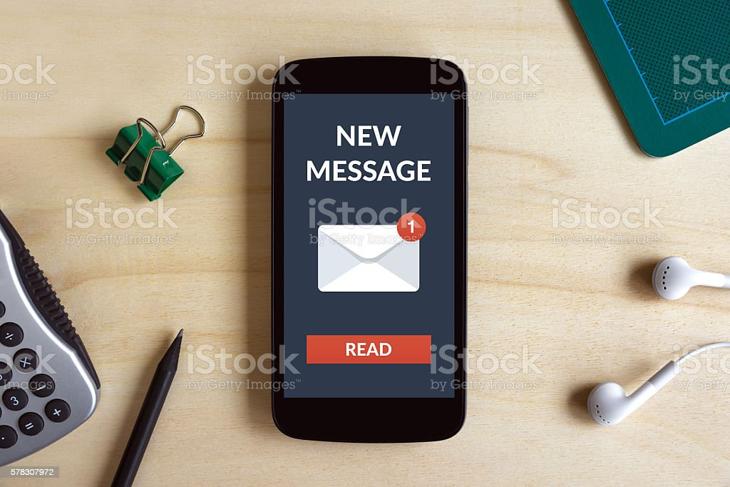 New message concept on smart phone screen on wooden desk stock photo