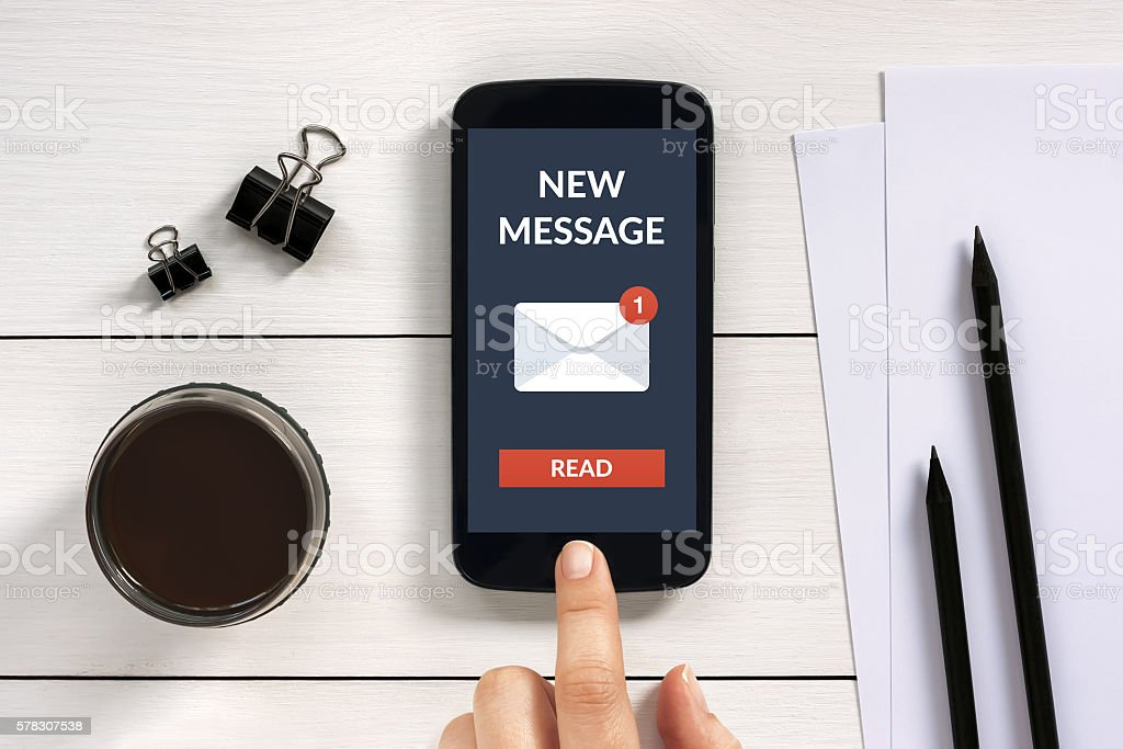 New message concept on smart phone screen with office objects stock photo