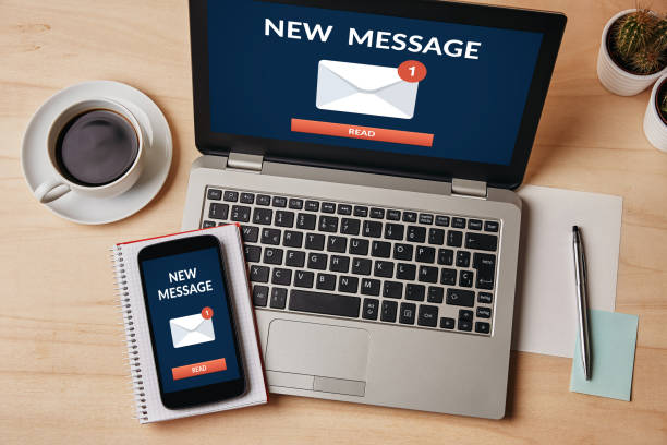 New message notification concept on laptop and smartphone screen stock photo