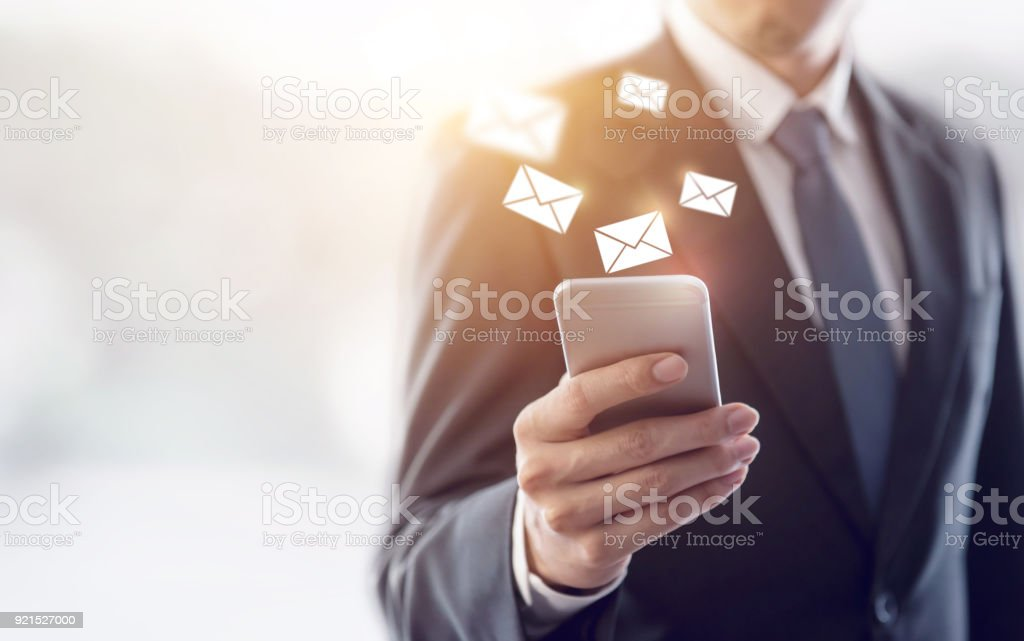New messages on mobile phone, hands of businessman opening inbox to...