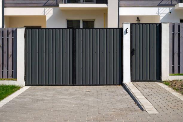new metal gates and a fence in front of the house. - portão imagens e fotografias de stock