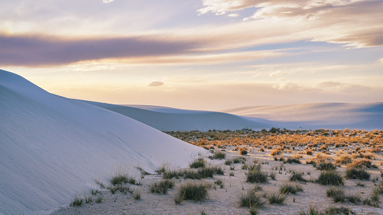 Sunset over New Mexico White Sands National Monument. The White Sand Desert Dunes in moody dusk twilight. Light and Shade over majestic white sandy desert dunes of the White Sands National Monument - National Park under colorful moody dusk twilight. White Sands National Monument, New Mexico, USA, North America