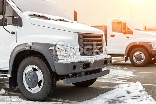 1140988145 istock photo New middle size trucks at dealership parking outdoors at winter. Truck service and maintenance. Delivering and warehouse service 1136788909