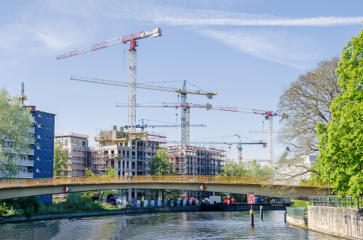 New modern buildings and cranes from the river Spree with the footbridge Wullenwebersteg in Berlin, Germany