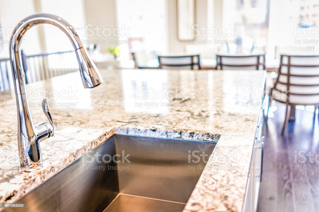 New modern faucet and kitchen room sink closeup with island and granite countertops in model house, home, apartment stock photo