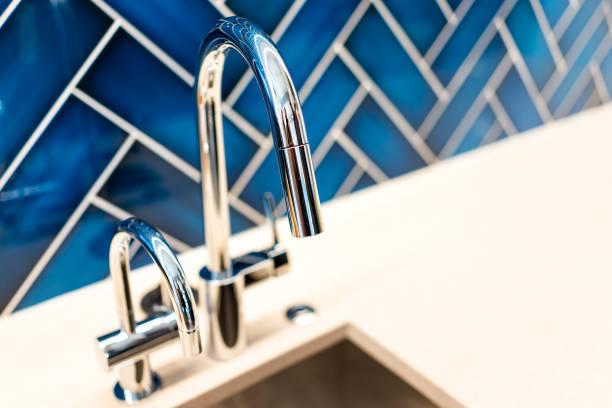 Close up moderno novo do dissipador da torneira e de cozinha com bancada, backsplash vibrante azul e punho de aço inoxidável limpo brilhante - foto de acervo