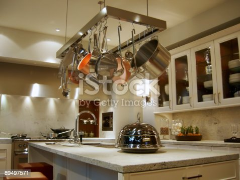 839034546istockphoto New, modern kitchen with a rack of hanging pots and pans 89497571