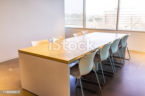 847512708 istock photo New modern office room in building with closeup of wooden meeting corporate business table by glass window and many chairs empty nobody 1135635572