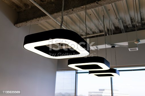 istock New modern office room in building with corporate business ceiling closeup of row of many square contemporary lights 1135635569