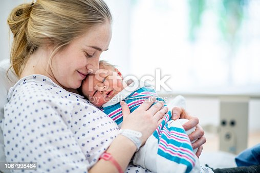 A caucasian mother in a hospital gown sits up in bed and holds her newborn baby to her chest