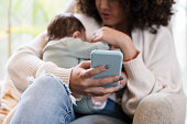 istock New mom uses smartphone while holding her baby boy 1209117996