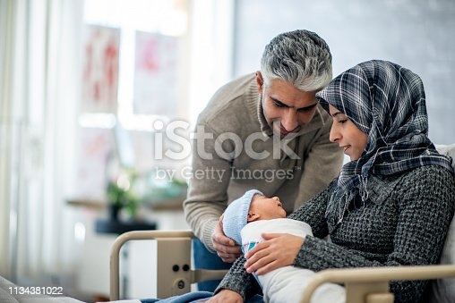 A mother and father are indoors in a hospital room. The mother is wearing a head scarf, and she is holding her newborn baby boy. The father is touching his son and watching him sleep.