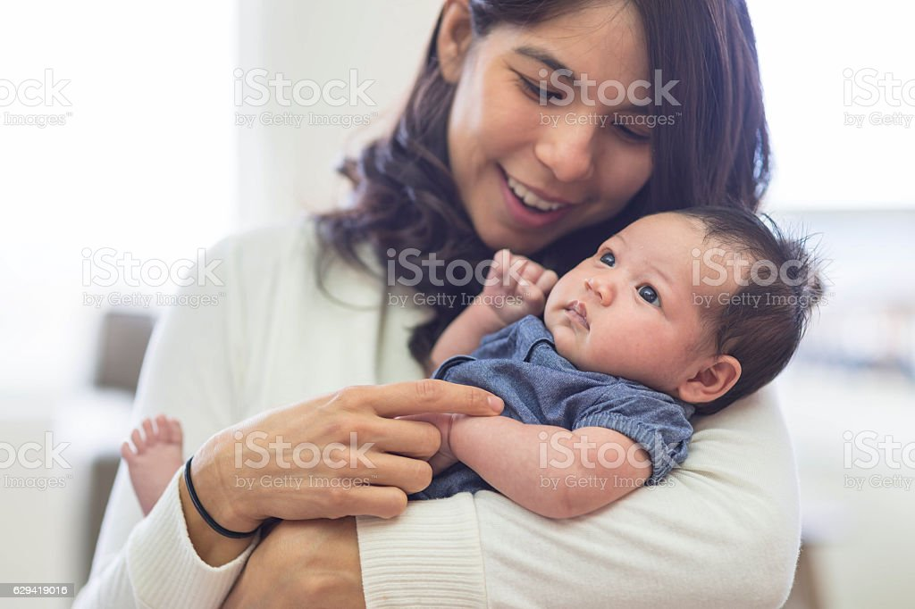 New mother smiling and holding newborn baby at home stock photo