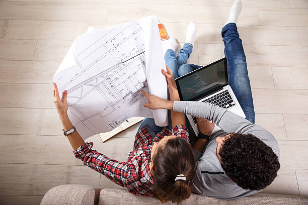 New nome Young couple sitting on the floor and looking at the blueprint of new home. modern period stock pictures, royalty-free photos & images