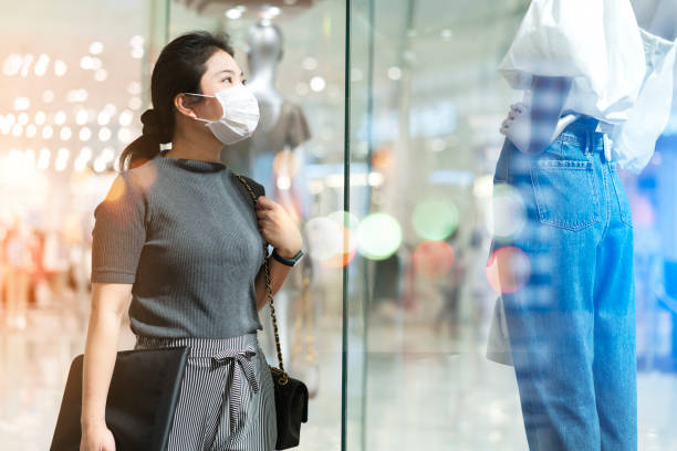 new normal after covid epidemic yound asian female wear face mask protection shopping dress or cloth in boutique shop new lifestyle in department store mall background - new normal foto e immagini stock