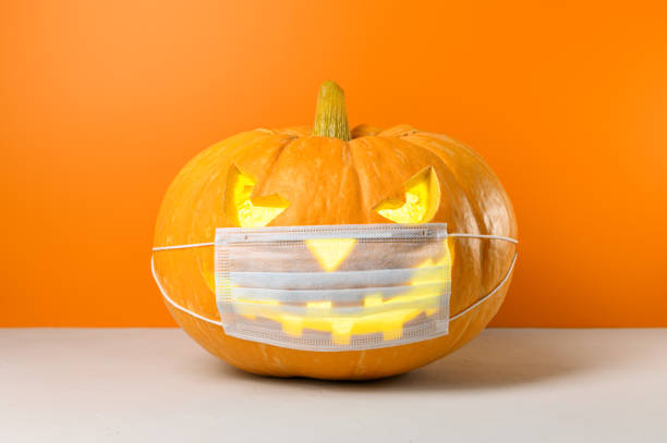 nuevo concepto normal. calabaza de halloween brillante en una máscara médica protectora sobre un fondo naranja. - halloween covid fotografías e imágenes de stock