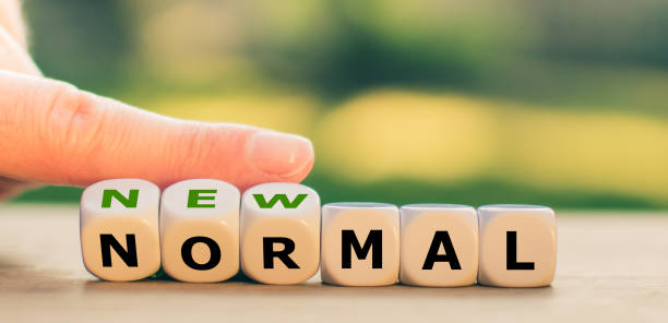 """New normal concept. Hand turns dice and changes the expression """"normal"""" to """"new normal"""". stock photo"""