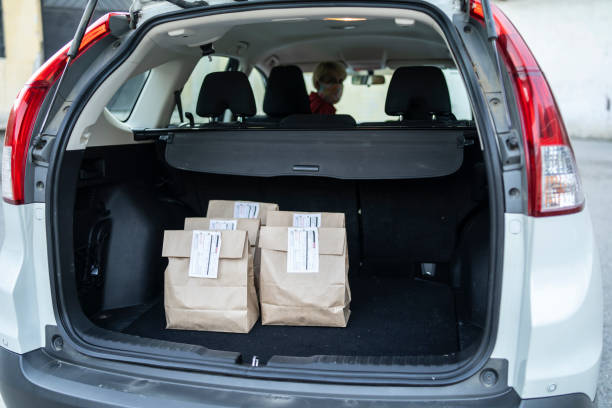 New normal: Curbside pickup for food delivery after Coronavirus pandemic Paper shopping bags loaded in the car by a curtsied service staff curbsidepickup stock pictures, royalty-free photos & images