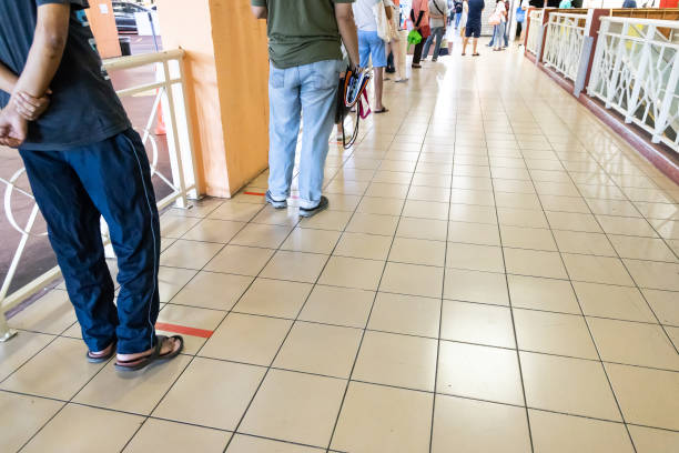 New normal lifestyle with social distancing where people are separated by a gap of at least 1 meter in queue into supermarket. stock photo