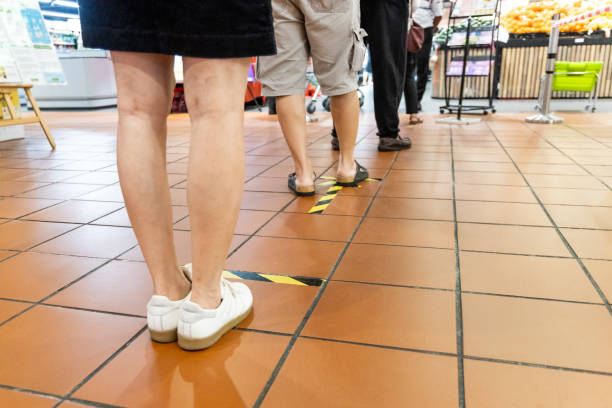 New normal social distancing with queue in line into supermarket stock photo