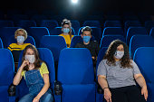 Group of people watching movie after  Coronavirus pandemic. Social distancing