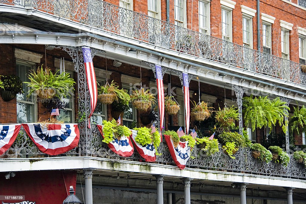 New Orleans balcony, wrought iron railing, flag banners, French Quarter stock photo