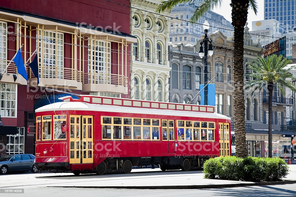 New Orleans Bright Red Streetcar Traveling Amid Palms and Flags stock photo