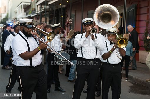 New Orleans, USA - Nov 3, 2018: A Second Line moving down Bourbon street in the french quarter late in the day.