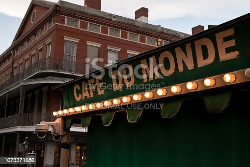 New Orleans, USA - Nov 6, 2018: The famous illuminated Cafe Du Monde awning late in the day with the Pontalba Buildings. The cafe is world renowned for its fluffy Beignets and Chicory coffee.