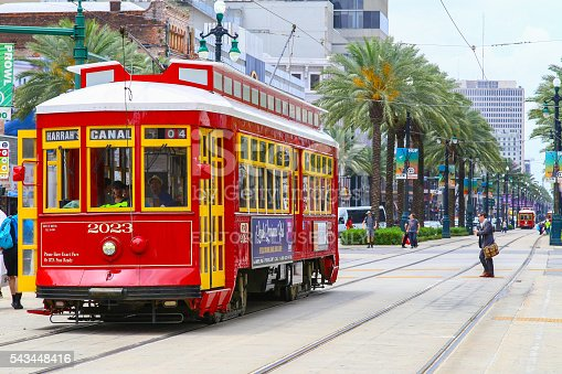 New Orleans, United States - May 14, 2015: Red streetcar on Canal Street, in the back another streetcar approaching and people crossing the street.