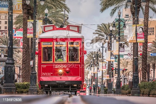 New Orleans, USA - October 05, 2016 : Famous streetcars of New Orleans driving in Canal Street during a bright spring day.  people are running along the railway which is very beautiful and filled with aligned palms