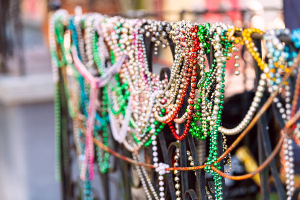 New Orleans, USA closeup of mardi gras beads hanging on fence by colorful building house and nobody on sidewalk stock photo