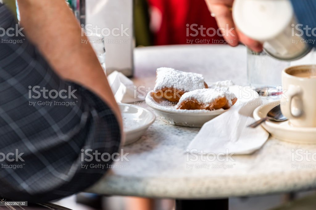 New Orleans, USA Famous cafe restaurant in Louisian old town city with people sitting at tables eating popular pastry beignets donut stock photo